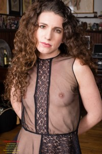 Laura, prisoner in a sheer blouse top, hands locked behind her