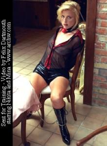 Nikita handcuffed and leg-irons in her prisoner's uniform