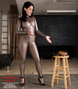 Wearing a sheer metallic catsuit, bondage slave Tilly McReese draws out attention to the set of transport shackles she is to be locked into.