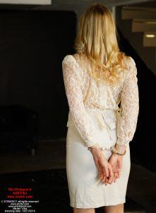 "Vika handcuffed in alternate court clothes, a sheer blouse and white pencil skirt with wrists locked behind her back, in ""The Prisoner 6 with Vika"""