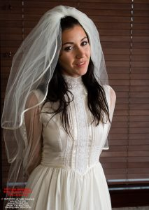 "Paisley has starred in ""Sent for Bondage 2"" and ""Sent for Bondage 3"". In this image, she appears as a handcuffed bride, but she is also in the videos nude, in plastic and spread. She also undergoes Gorean Slave Training."