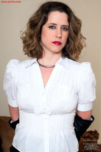 Chastity Belt Fitting in Bondage. A female slave dressed in a cap-puff sleeved business blouse, gloved in leather, with wrists handcuffed behind her