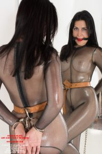 Wearing a sheer metallic catsuit, bondage slave Tilly McReese is imprisoned into the set of transport shackles. - student loan slave