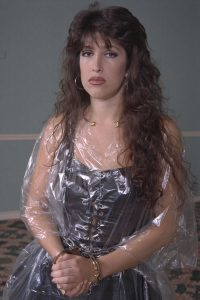 Bondage model Alexis wearing her black latex stripper uniform, clear plastic raincoat, handcuffed, with cuffs chained to her waist