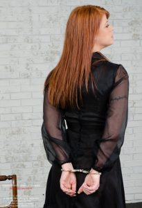 Angela Orlando, handcuffed in receptionist uniform