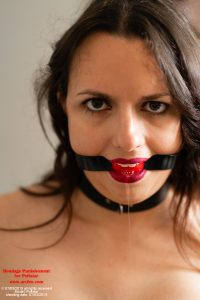 Polistar topless in leather gloves and skirt - her wrists and handcuffed behind her back and she is ball-gagged, drooling