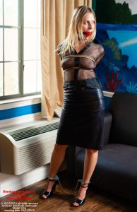 The Prisoner Vika in sheer black blouse, leather skirt, tightly bound and gagged, with leg-irons