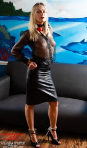 Vika in black organza blouse, with leather skirt, high heels. She is collared, shackled and has a ball-gag around her throat
