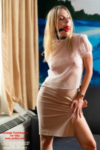 The bondage prisoner Vika in a sheer white organza blouse with puff sleeves. She has a respectable tan skirt and is collared and ball-gagged